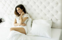 Junge Frau sitzt im Bett (Foto: © boggy22, Fotolia)
