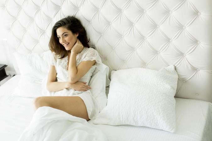 Junge Frau sitzt im Bett