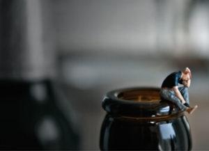 Betrunkene Frau sitzt auf Flaschenrand (Foto: Blau_Am Rand © DAK Gesundheit)