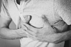 Mann erleidet einen Herzinfarkt und greift sich an die Brust