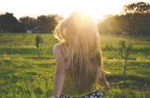 Frau läuft auf einer Wiese durch die Sonne