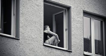 Frau sitzt am Fenster und denkt nach
