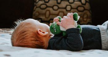 Baby liegt auf dem Rücken und hat ein Spielzeug in der Hand