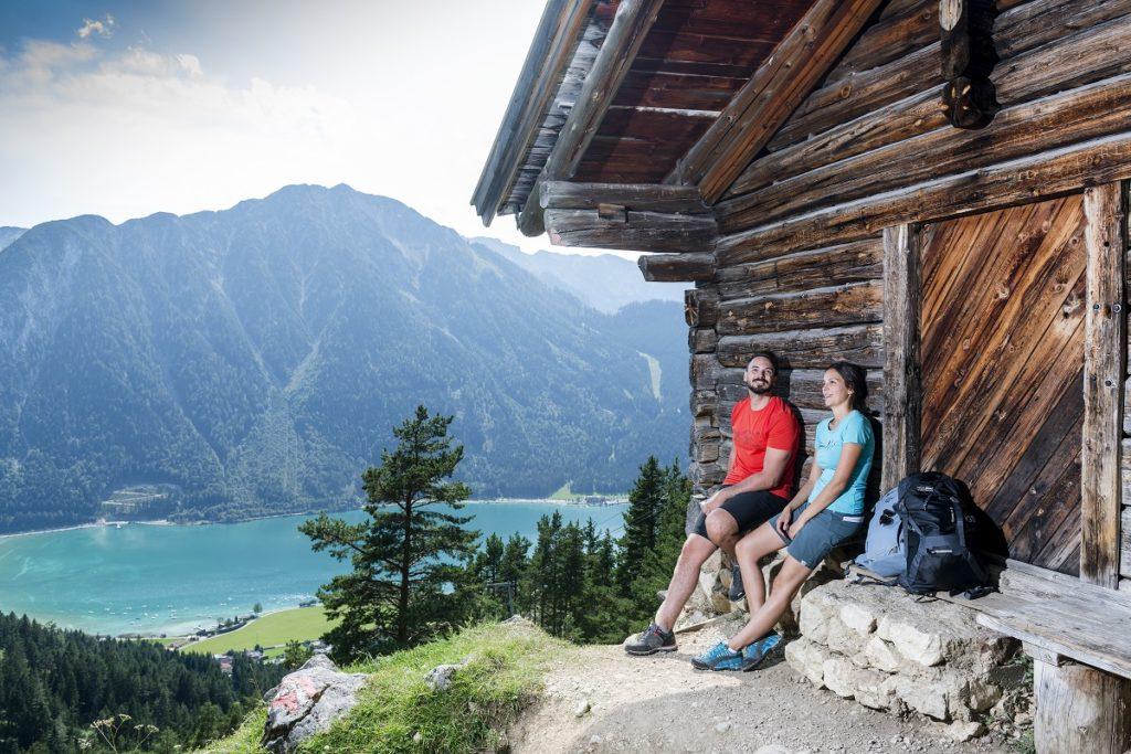 2 Wanderer an einer Holzhütte mit Blick auf den Achensee