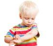 Kleine Kind schaut sich seine Verletzung am Arm an