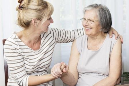 Frau hält die Hand einer älteren Frau