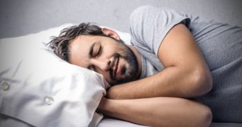 Mann im grauen T-Shirt schläft und grinst dabei