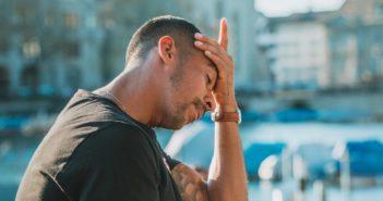 junger Mann mit chronischer Migräne sitzt draußen und fasst sich an den Kopf