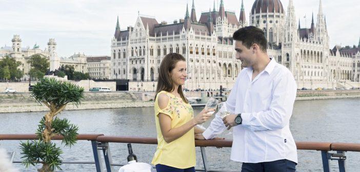 Ein Paar stößt an auf dem Sonnendeck der Primadonna, im Hintergrund das Parlament von Budapest
