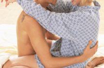 glückliches Paar sitzt umarmt im Bett - sexuelle Gesundheit