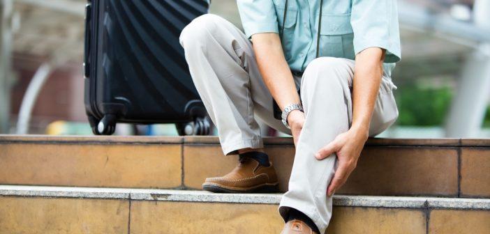 Person auf einer Treppe hält sich das Bein - Durchblutungsstörung in den Beinen