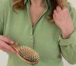 Frau mit Haarausfall hält eine Bürste in der Hand