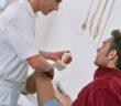 Arzt untersucht das Knie eines Patienten