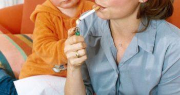 Frau rauchend neben einem kleinen Kind